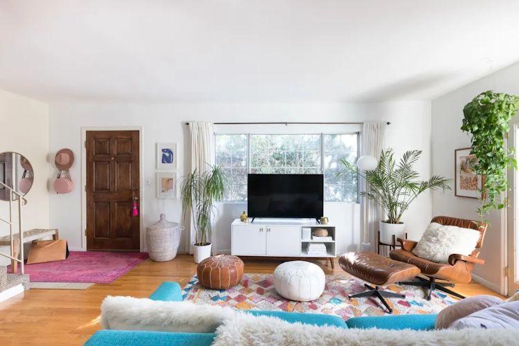 Distribución de la sala, con el sofá ubicado a lo ancho frente a un mueble de TV de diseño mid century