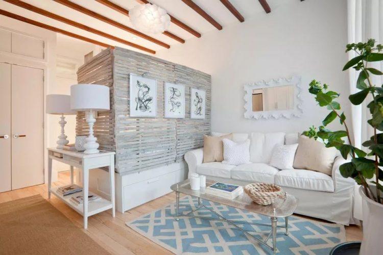 Divisor de madera rústico sujetado a la base de la cama. Una forma de dividir y a la vez decorar espacios.