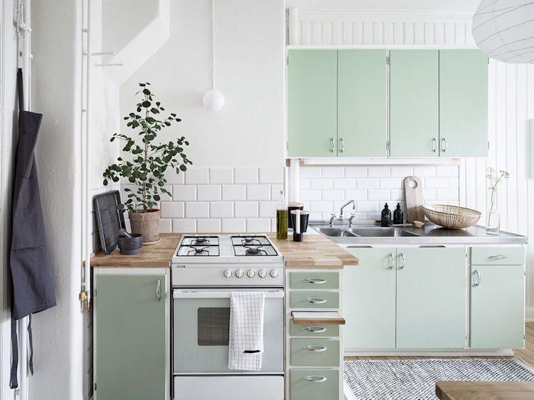 Cocina de diseño escandinavo con muebles en color menta y mesadas que combinan madera con acero inoxidable