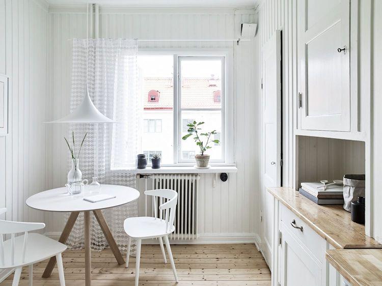 Cocina con comedor diario de estilo escandinavo con paredes revestidas en madera