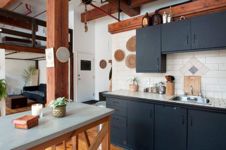 Una mesa alta con tapa de concreto pulido sirve tanto para comer como para preparar comidas, al modo de isla de cocina