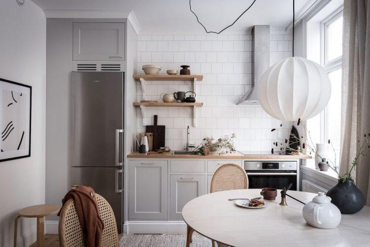 Muebles de cocina en color gris, encimera de madera y revestimientos blancos crean un conjunto neutral pero con estilo en la cocina