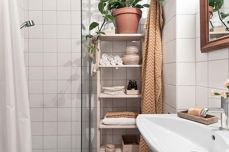 Pequeño cuarto de baño en blanco con detalles en madera.