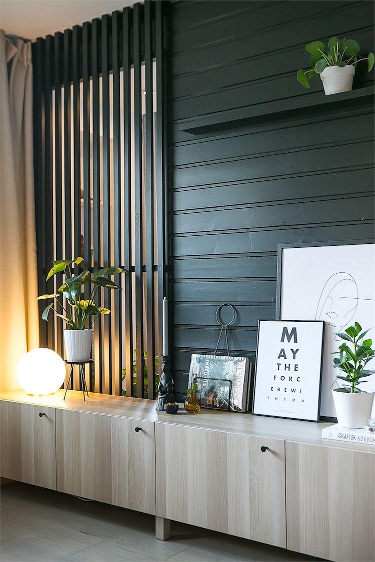 Pared de madera que divide la sala del comedor. Pintada de negro acentúa la decoración masculina del departamento.