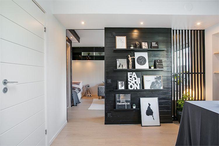 Comedor separado de la sala mediante pared de madera que alterna espacios sólidos con otro que deja pasar la luz.