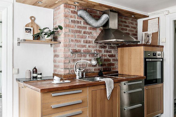 La pared de ladrillo visto se combina con los muebles de cocina revestidos en madera para crear una decoración cálida.