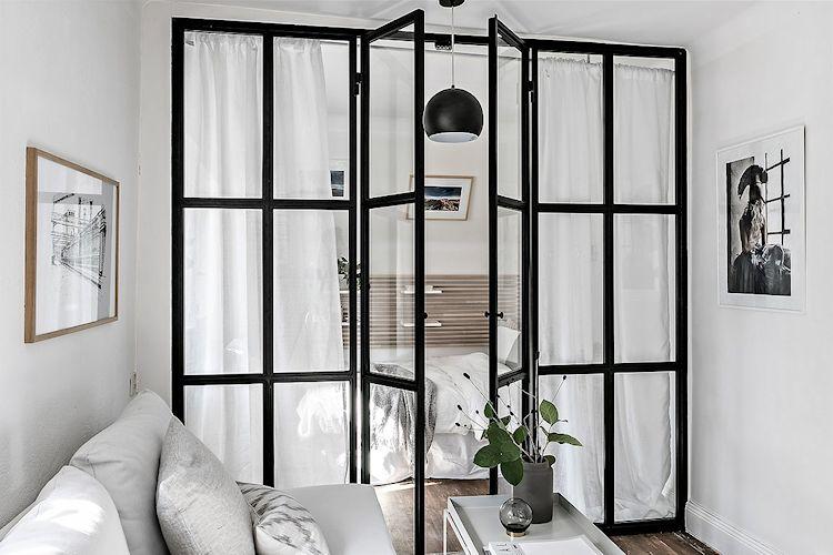 La recámara se separa de la sala mediante una estructura metálica de vidrio repartido.
