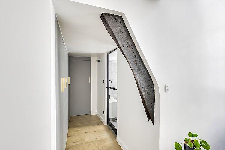 Hall distribuidor que comunica la sala con el baño, con vigas expuestas de madera y muchos clósets.