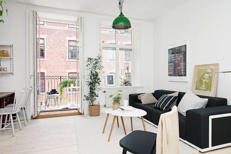 Sofá contemporáneo y conjunto de mesas escandinavas configuran la sala del estudio