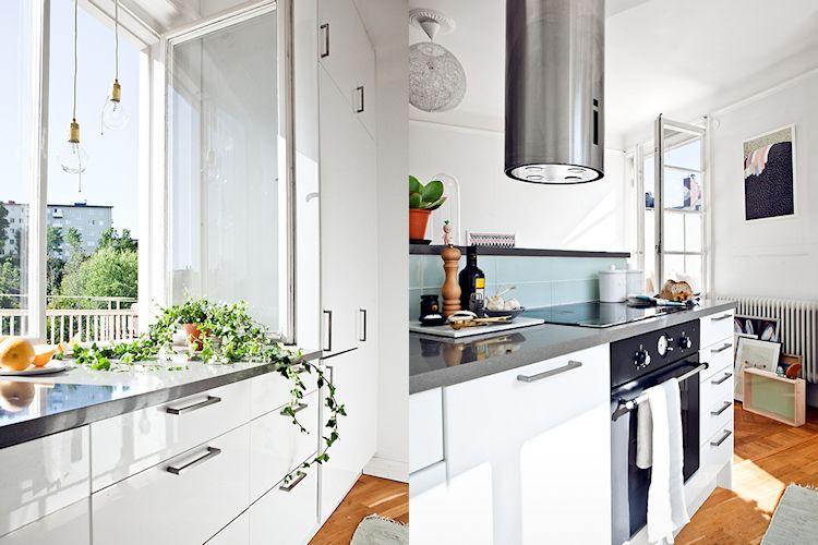 Muebles de cocina blancos brillantes y artefactos en acero inoxidable dan un look moderno a la cocina
