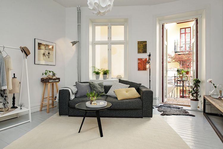Sala con decoración sencilla donde contrastan colores oscuros y claros, clásico del estilo escandinavo