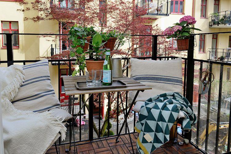 Balcón pequeño decorado con macetas colgantes y muebles plegables