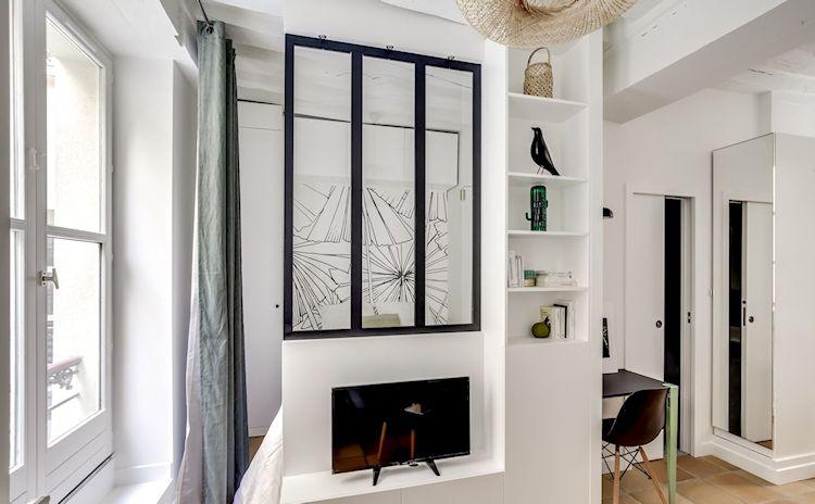 Pared divisoria con parte superior vidriada para separar la sala de la recámara.