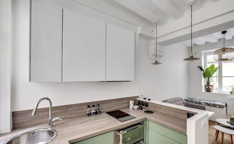 Cocina pequeña con diseño en forma de U, muebles coloridos y encimera de madera.