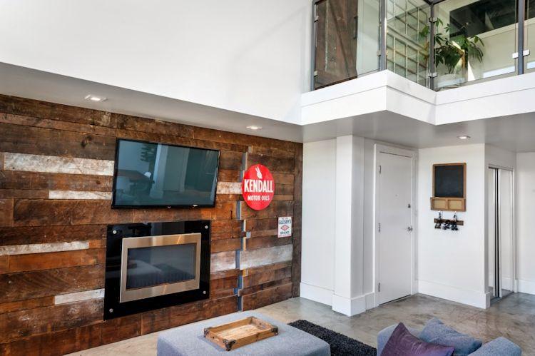 Sala del loft con pared que la separa del escritorio revestida en madera rústica recuperada de la construcción original