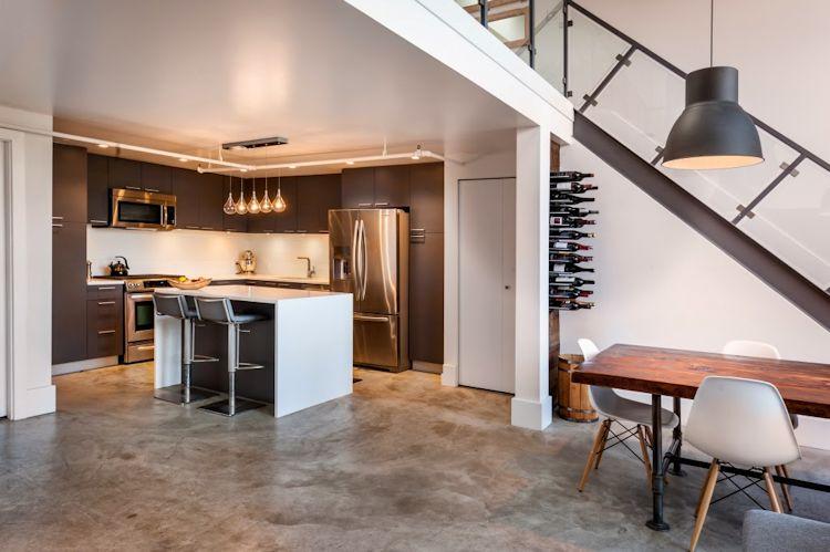Cocina moderna con muebles oscuros y encimeras blancas
