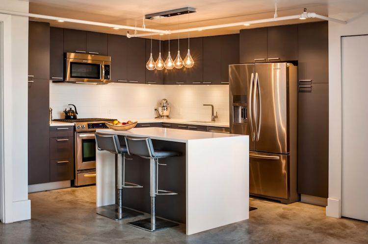 Isla de cocina y barra desayunadora. Original iluminación que recorre el espacio a través de una tubería
